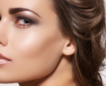 Glamour portrait of beautiful woman model with fresh daily make-up and romantic wavy hairstyle. Fashion shiny highlighter on skin.